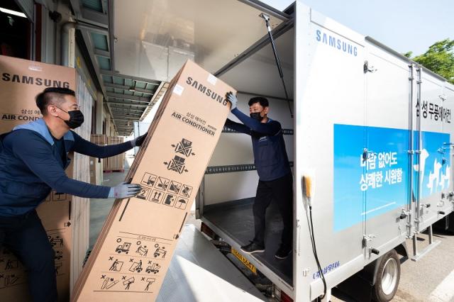 경기도 수원시 영통구에 위치한 삼성전자로지텍 수원센터 물류창고에서 담당자들이 삼성 '비스포크 무풍에어컨'을 배송하기 위해 차량에 싣고 있다. <사진제공=삼성전자>